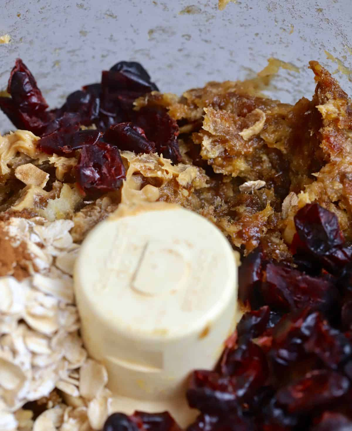Chopped dates, oatmeal, dried cranberries and peanut butter in the bowl of a food processor.