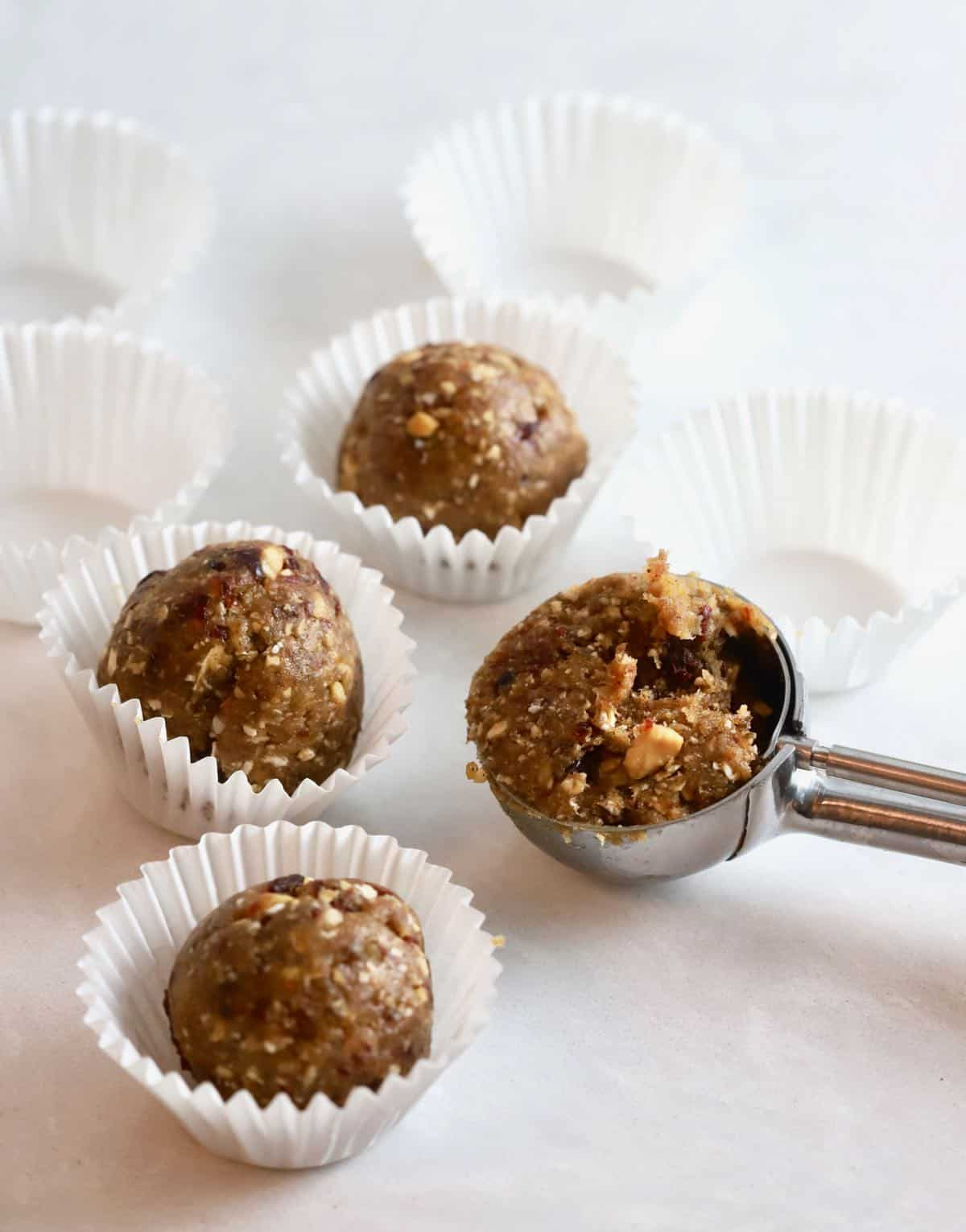White mini cupcake liners with a oatmeal energy ball in them.