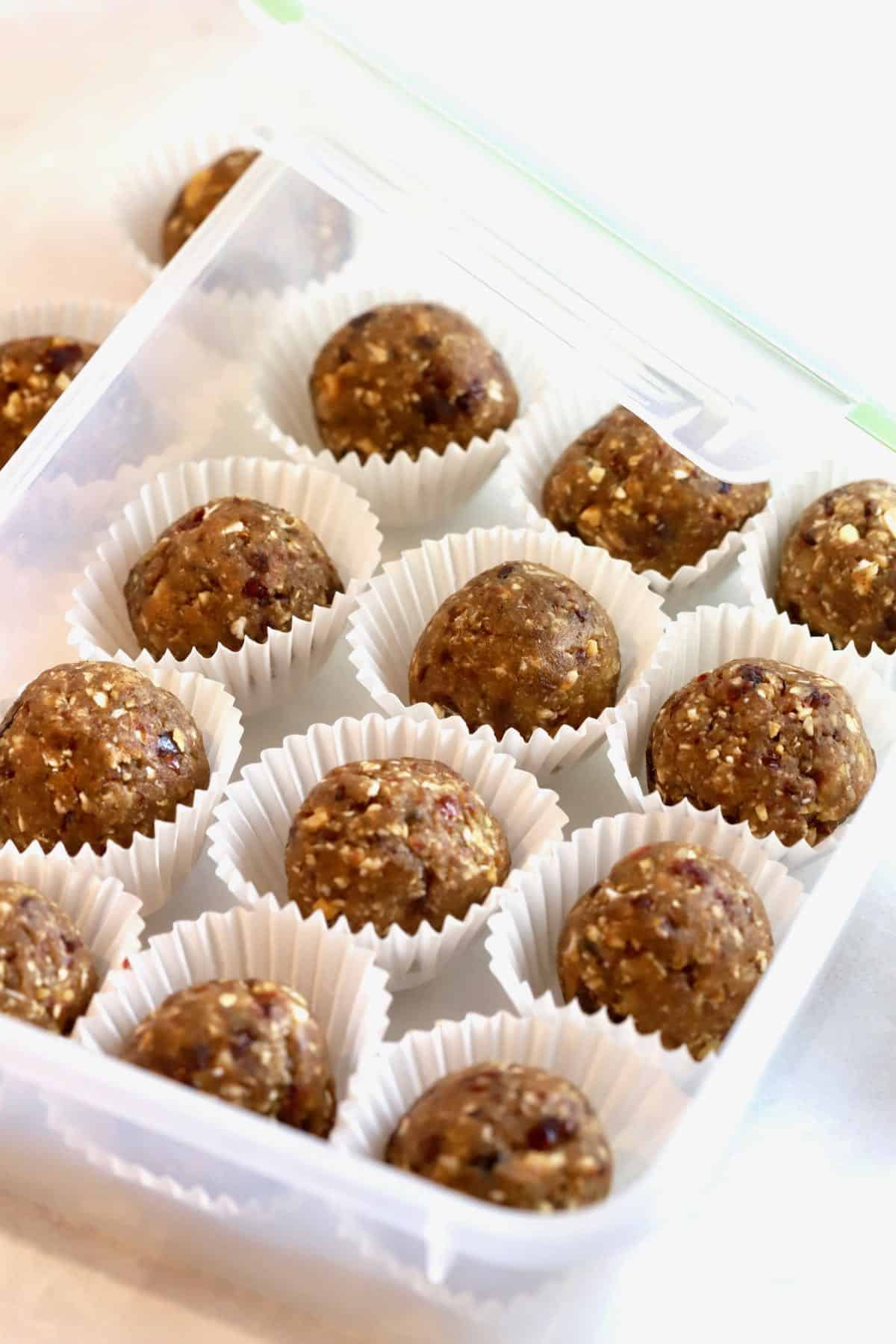 A plastic storage box full of the oatmeal energy balls in muffin liners.