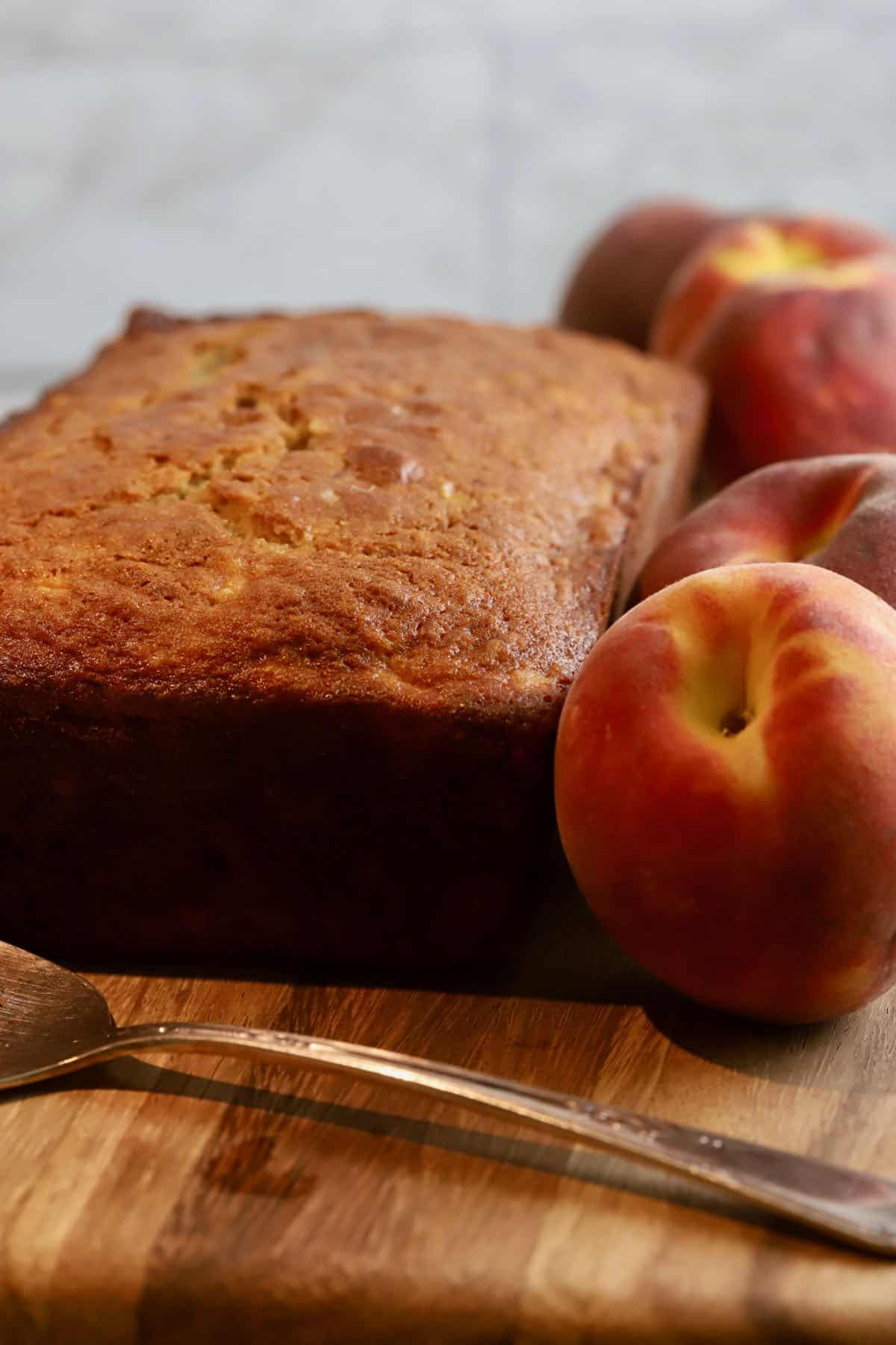 A loaf of peach bread on a wooden cutting board.