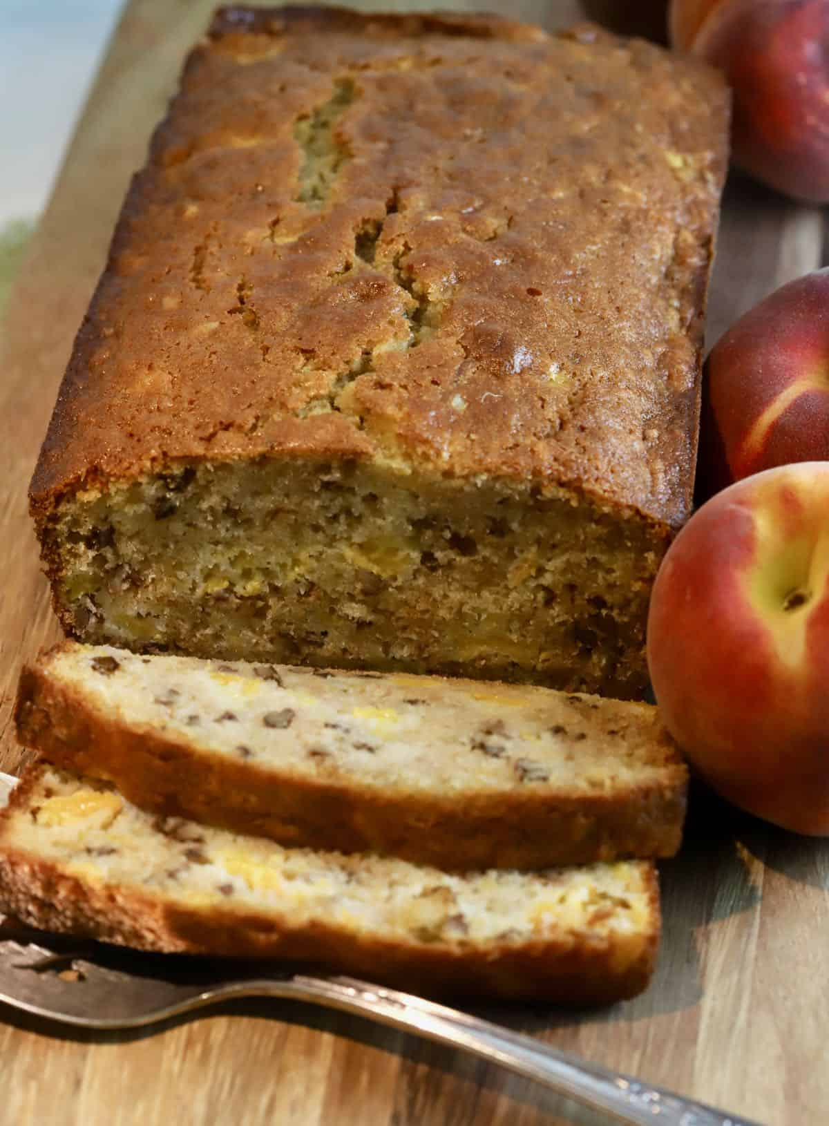A loaf of quick bread on a cutting board with peaches.