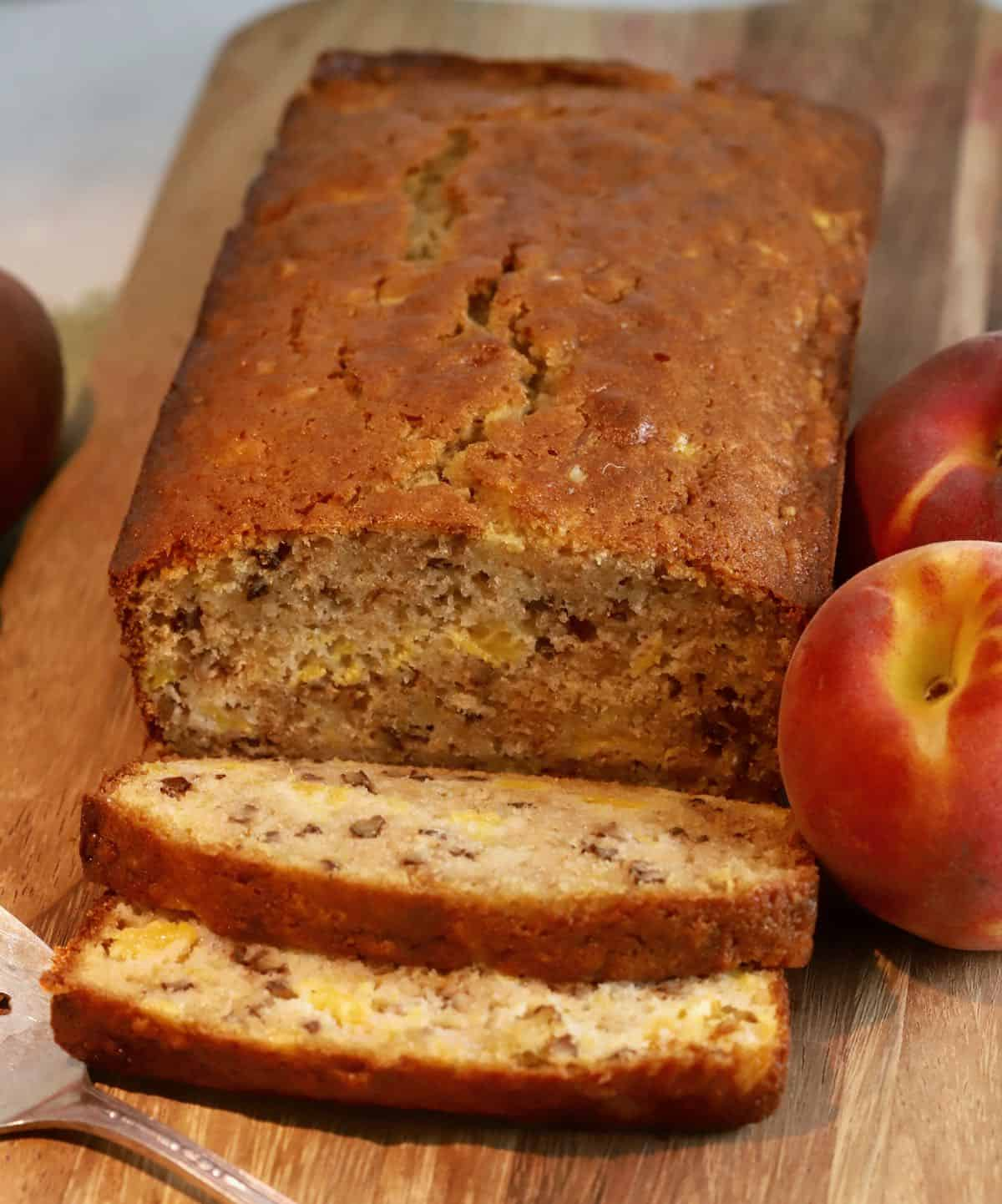 A loaf of peach bread with slices cut.