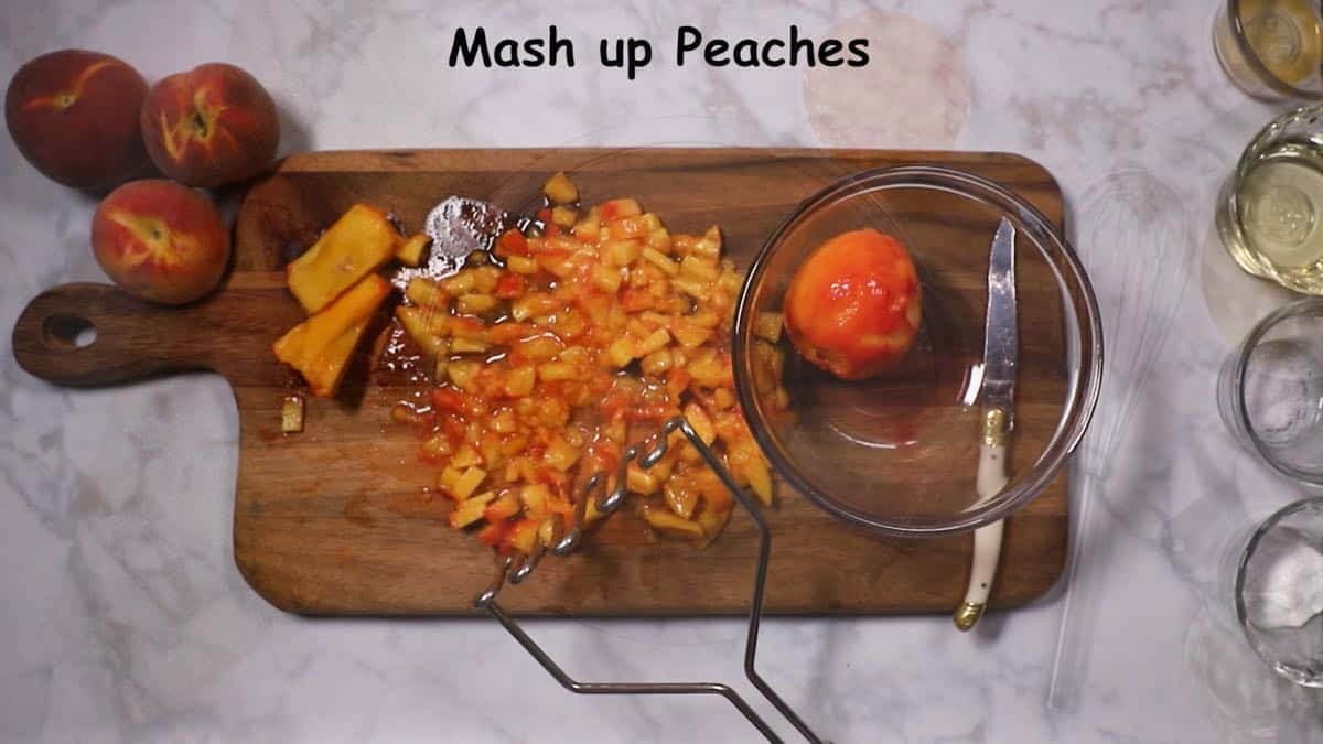 Mashing pieces of peaches on a wooden cutting board.