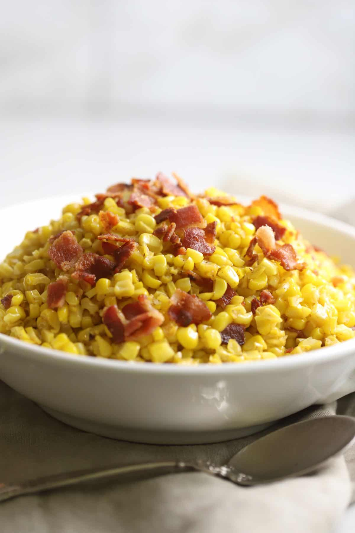A large serving dish full of fried corn topped with bacon.