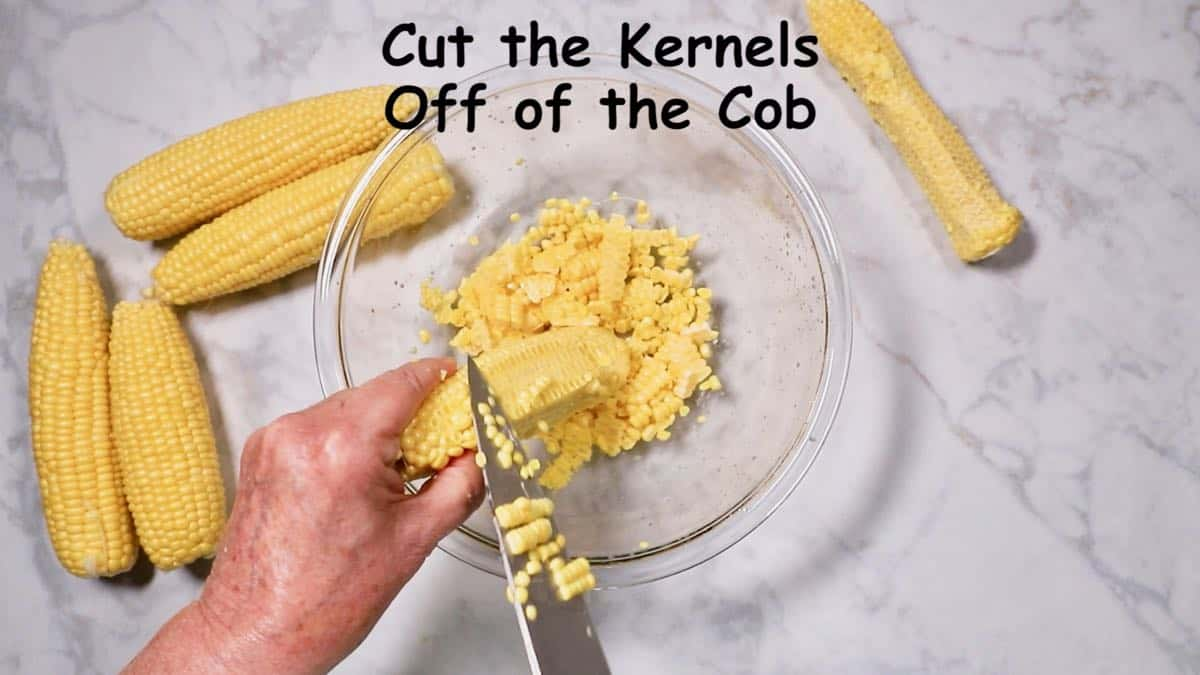 Using a knife to slice kernels off of an ear of corn.