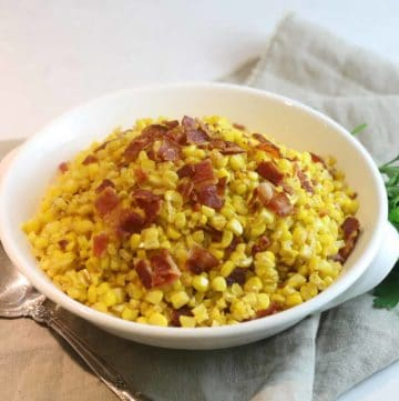 A white serving dish with fried corn topped with bacon.