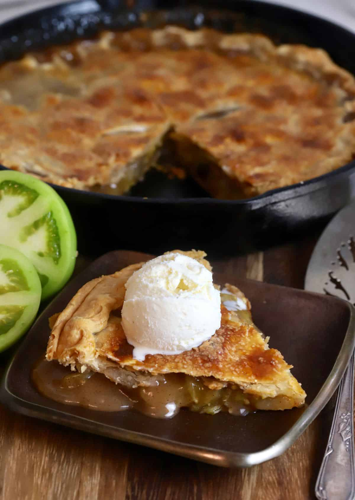 A cast-iron skillet with a slice of tomato pie cut out topped with a scoop of vanilla ice cream.