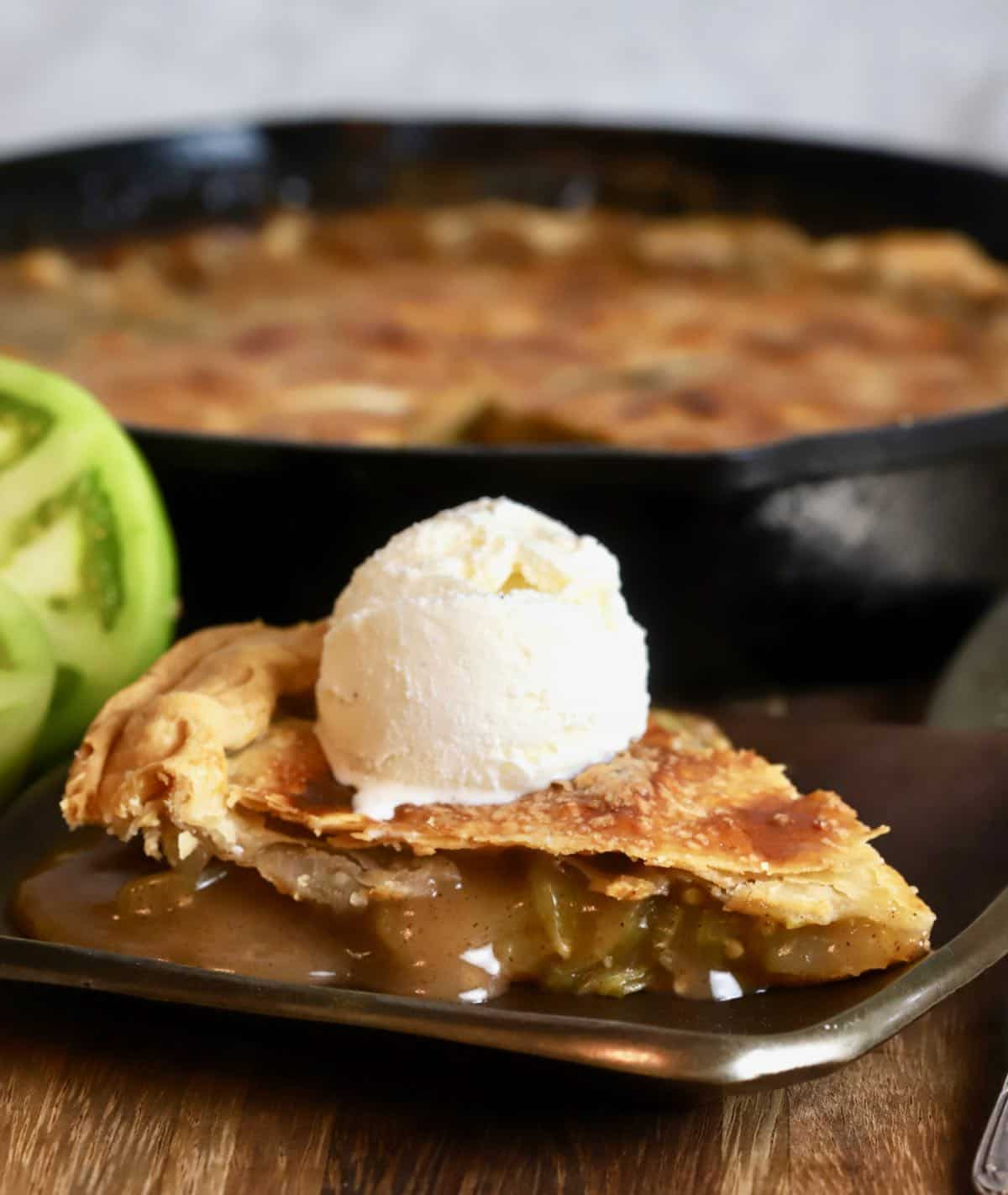 A slice of green tomato pie topped with a. scoop of ice cream