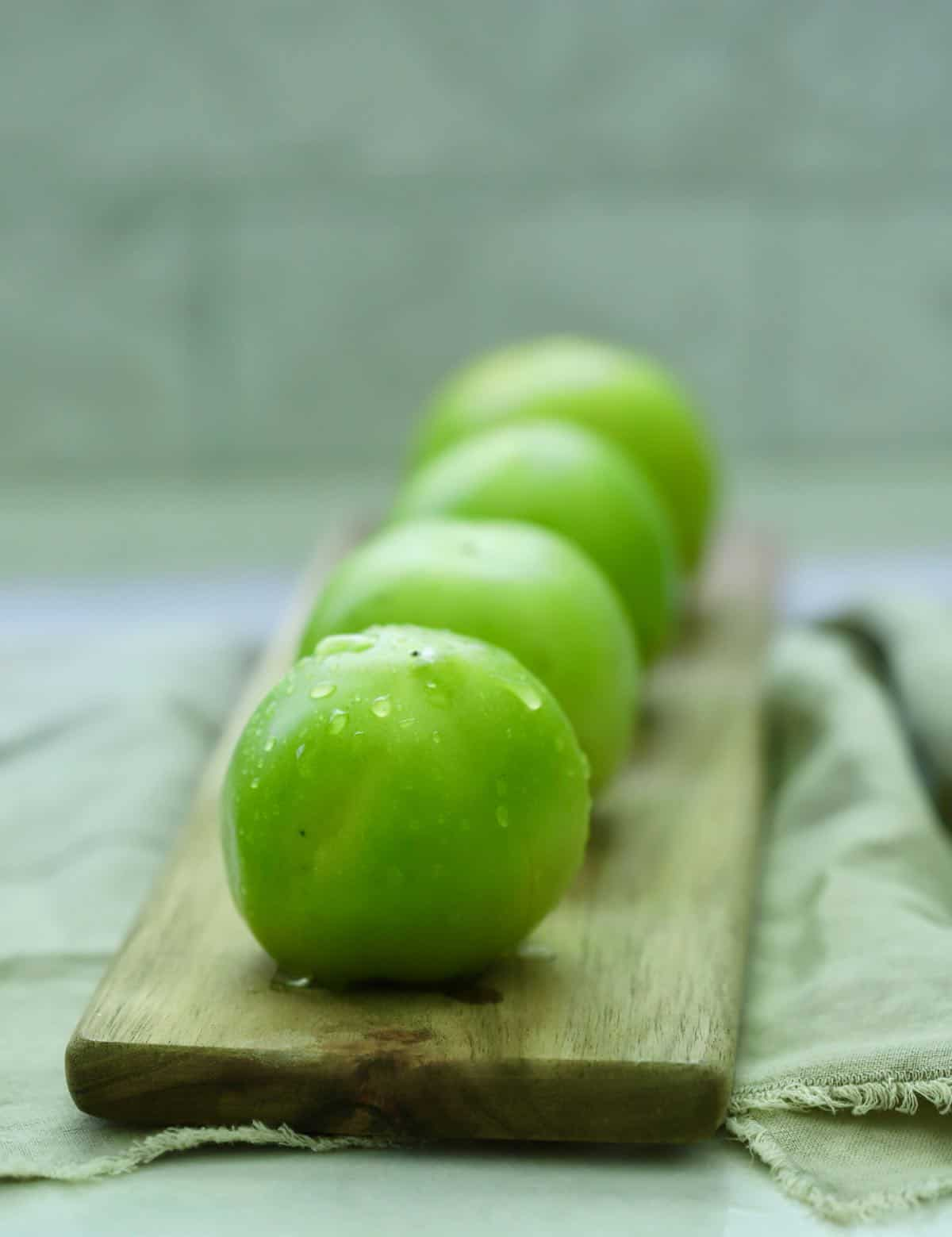 Four green tomatoes on a small cutting board.
