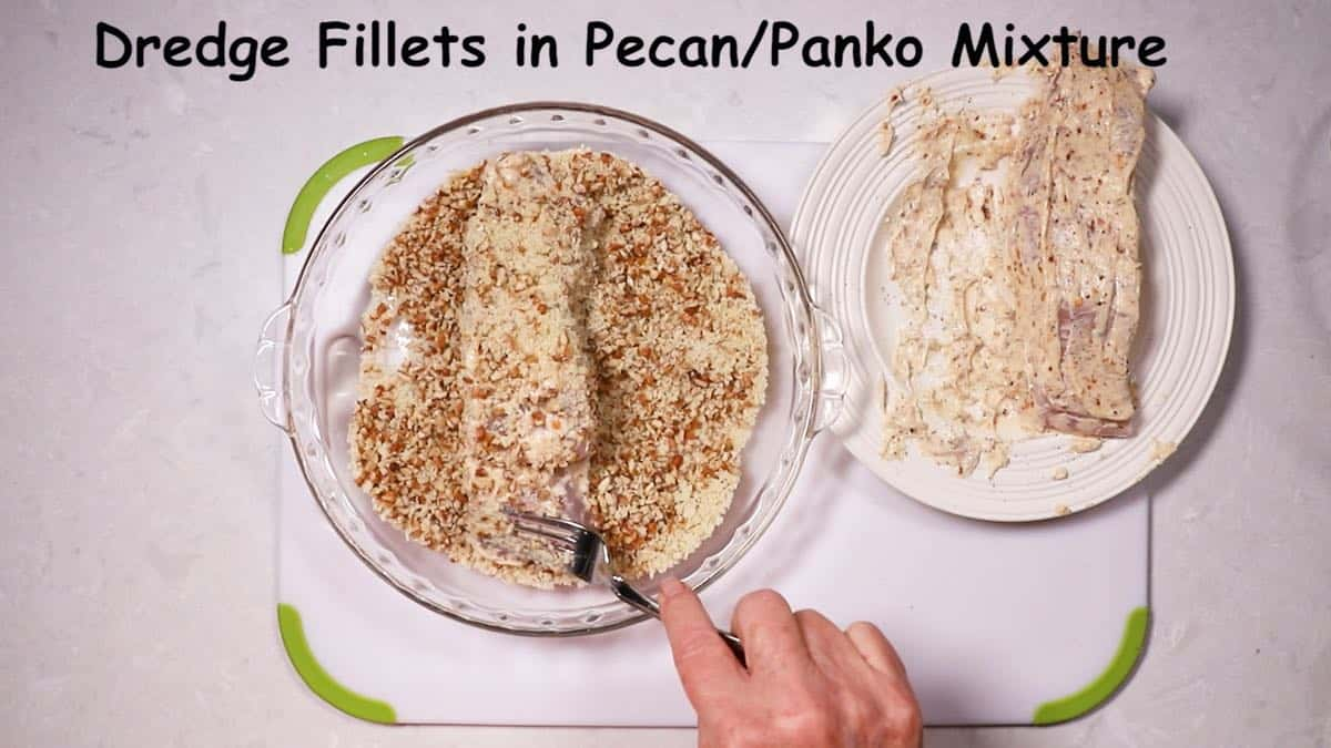A fish fillet being dredged in a mixture of pecans and panko.