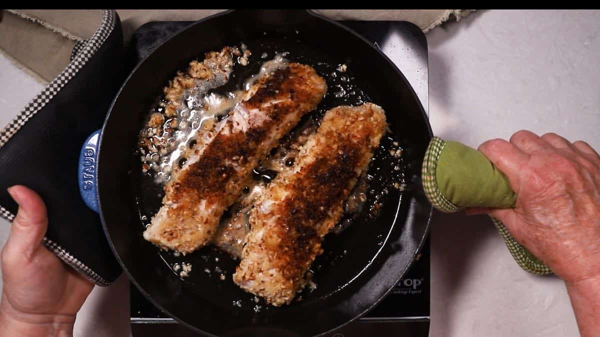 Two fish fillets cooking in a cast-iron skillet.