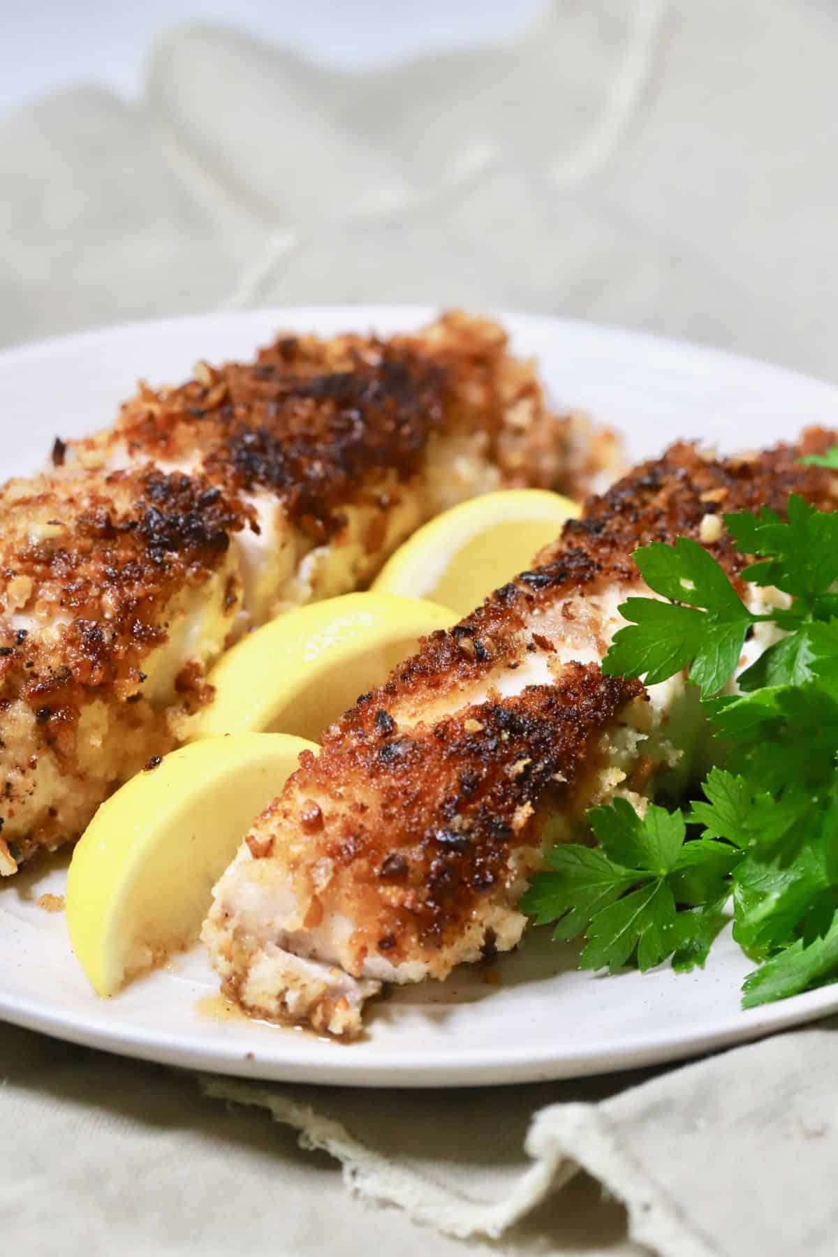 Two pecan crusted grouper fillets on a plate.