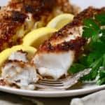 Pecan crusted fish fillets garnished with lemon slices.