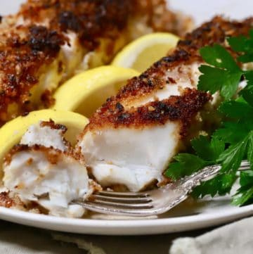 Pecan crusted fish fillets garnished with lemon slices.