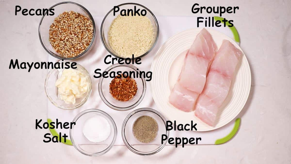 Two grouper fillets, panko, chopped pecans, mayonnaise and seasonings on a cutting board.