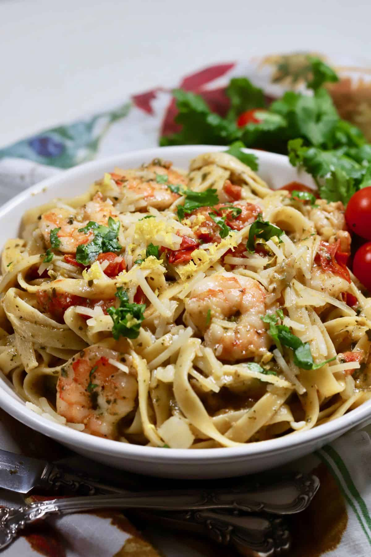 A white bowl with pasta and shrimp.