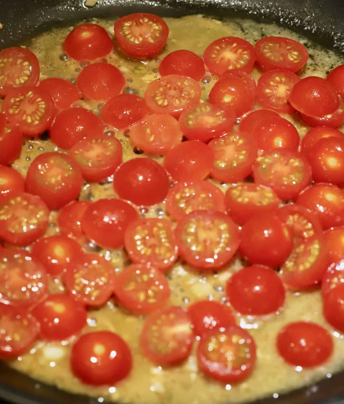Sliced cherry tomatoes cooking in a skillet.