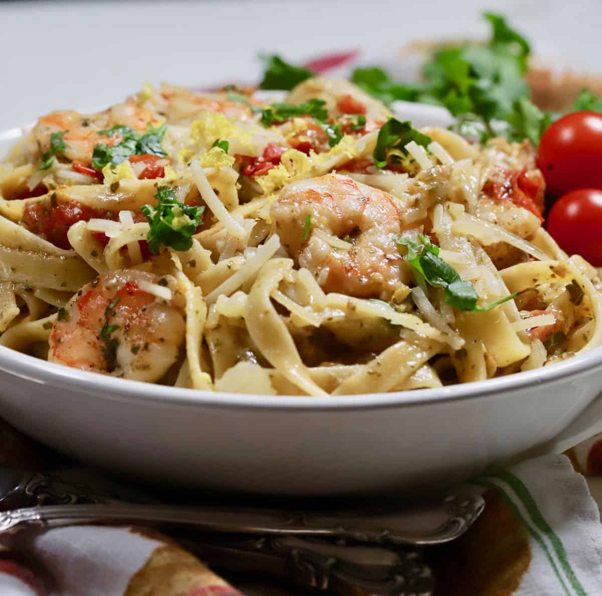 A large bowl with pasta, shrimp and tomatoes.