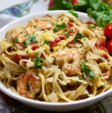 Pasta, pesto, shrimp and tomatoes in a large white bowl.