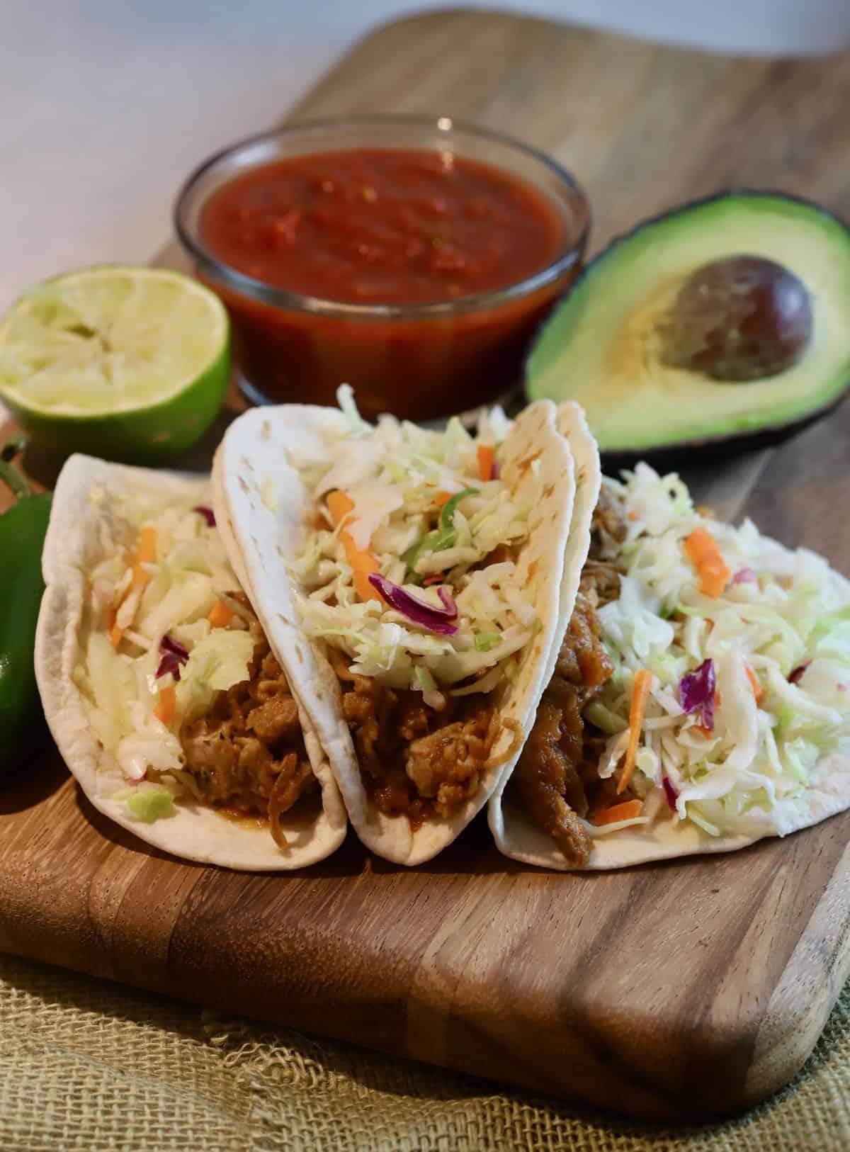 Three pork tacos on a wooden cutting board.