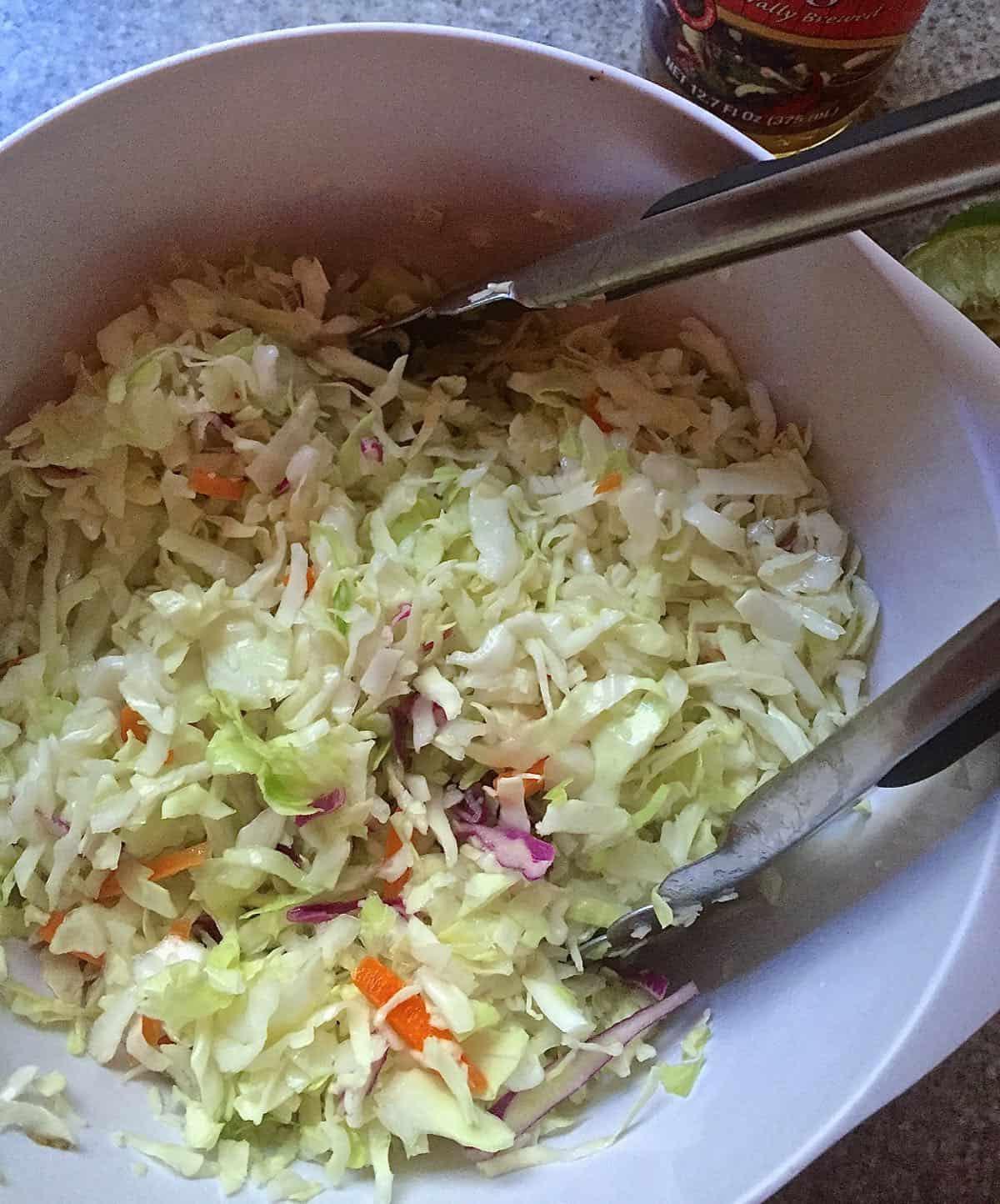 A white bowl full of coleslaw.