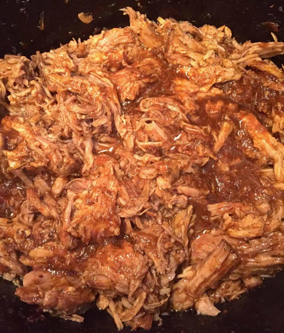 Shredded pulled pork in a crock-pot.