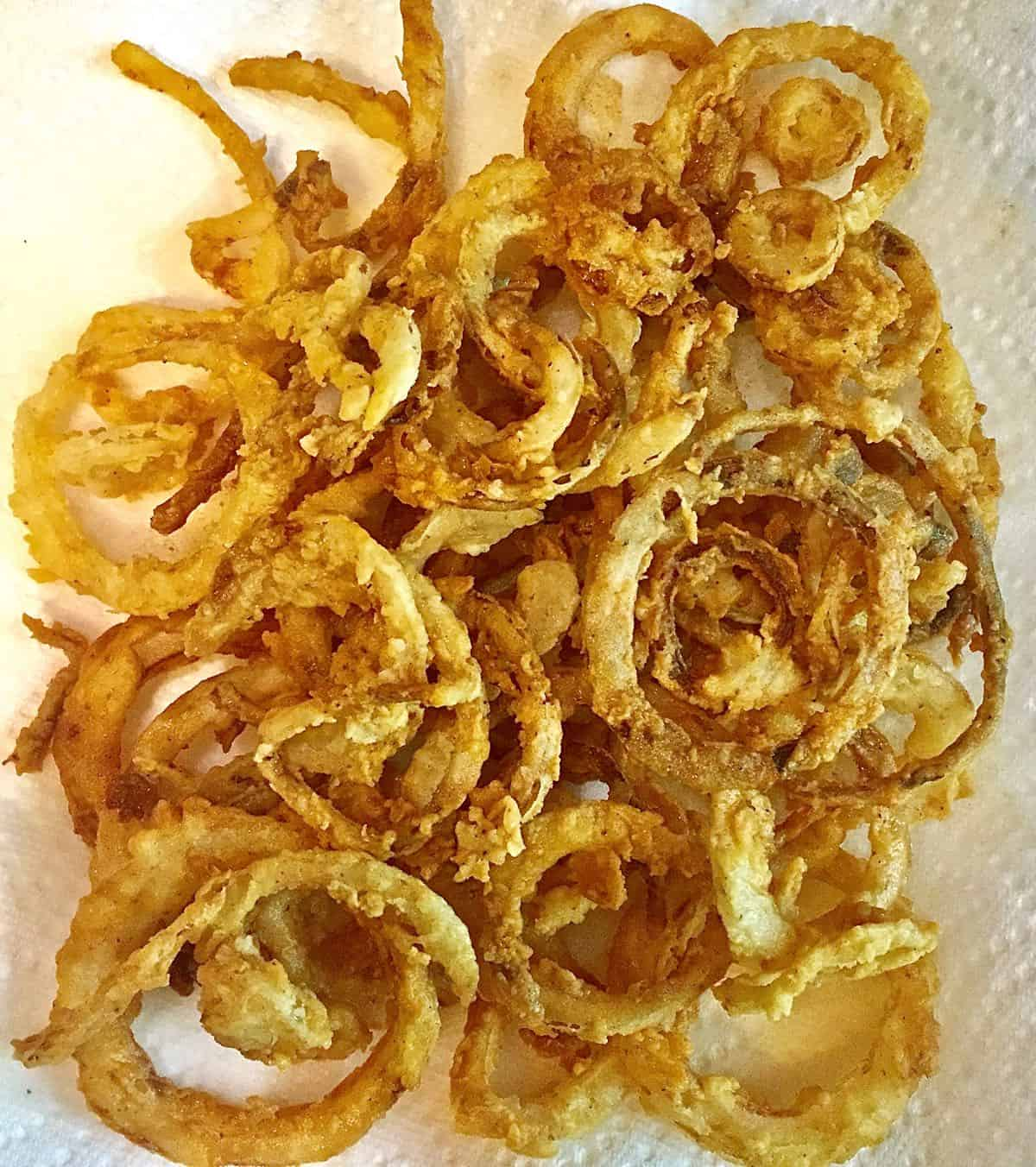 Fried onion rings draining on a paper towel.