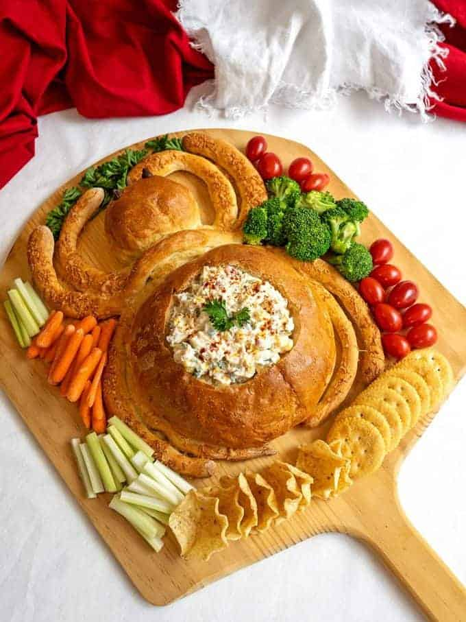 Bread shaped like a spider with dip and cut up veggies.