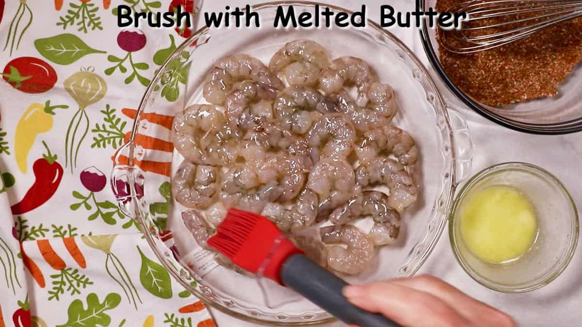 Brushing melted butter over shellfish in a dish.