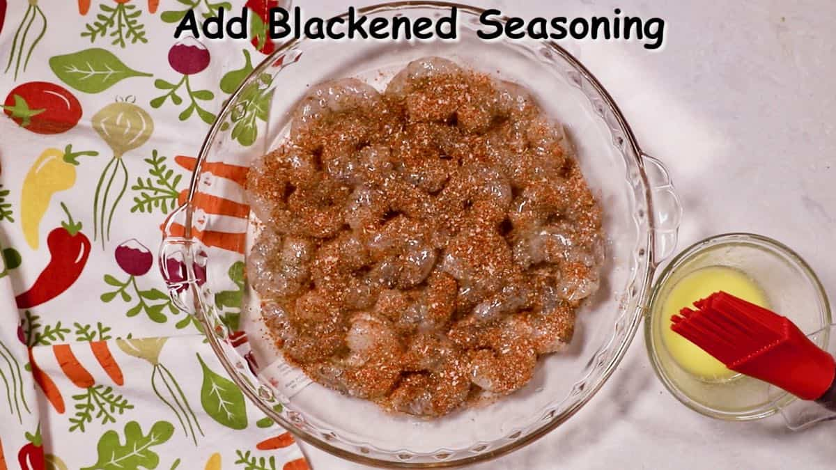 Blackening seasoning over shrimp in a dish.