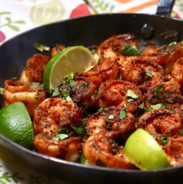 A cast-iron skillet full of blackened shrimp and garnished with lime slices.