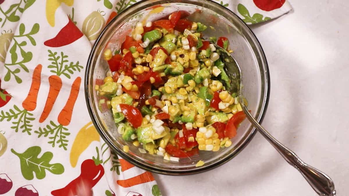 Avocado salsa in a clear glass bowl.