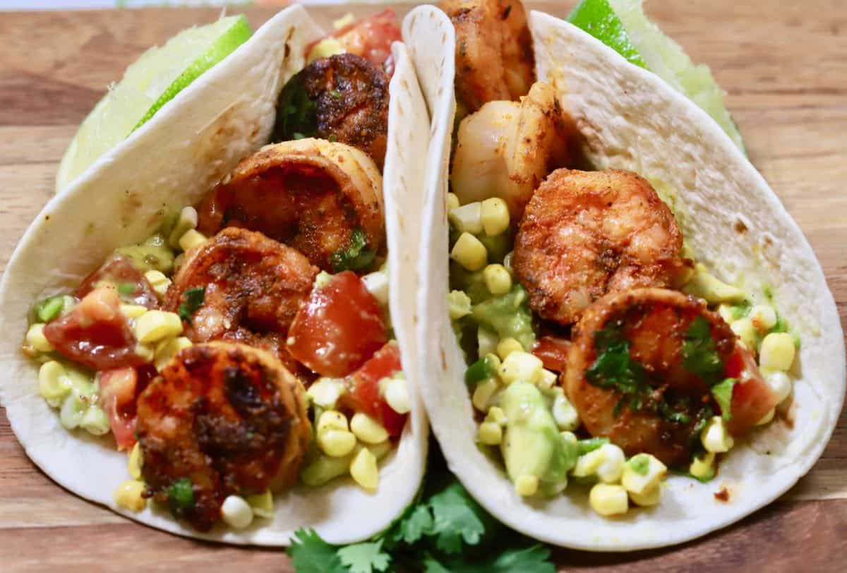 Two shrimp tacos with corn and avocado.