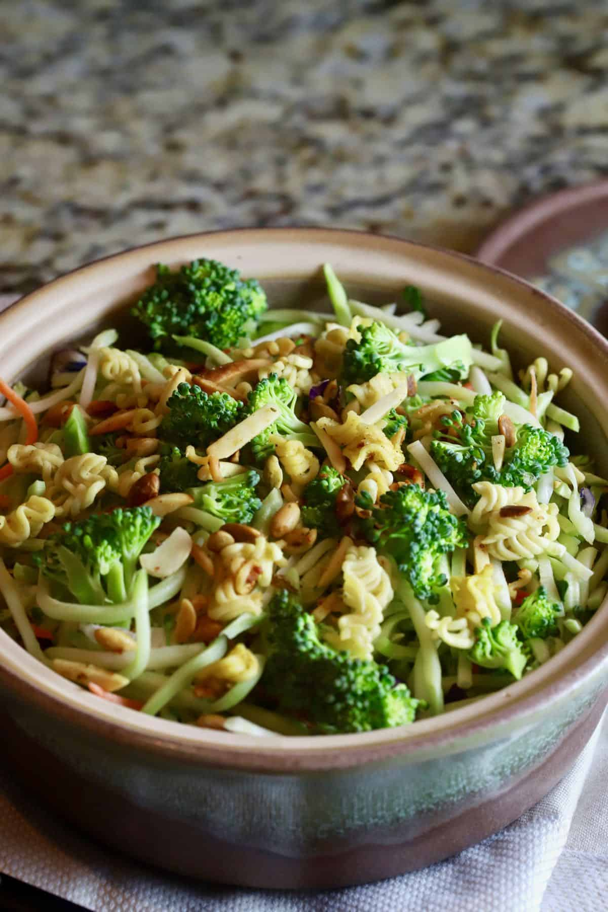 Broccoli florets, slaw and ramen noodles in a pottery bowl ready to serve.