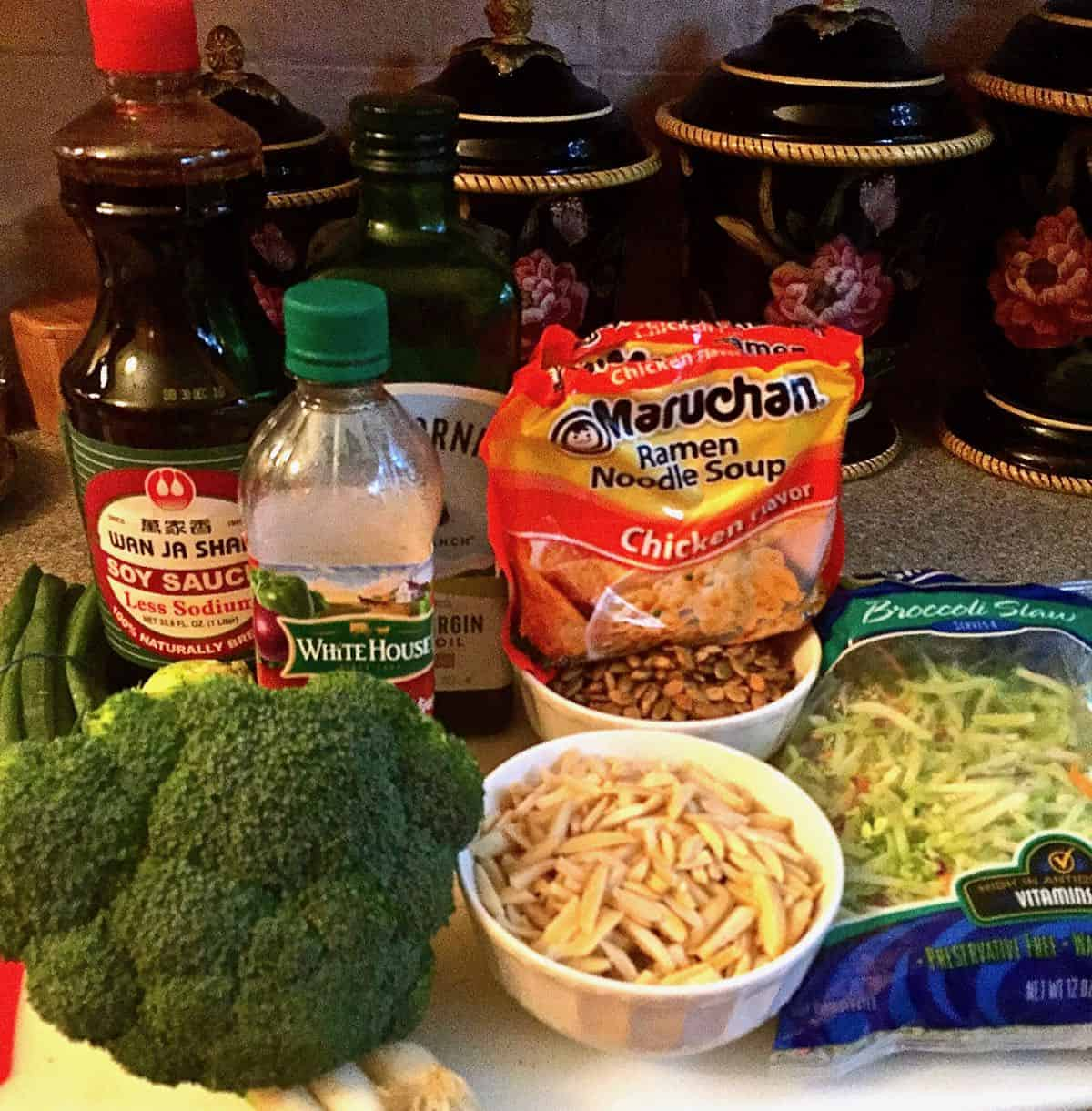 A head of broccoli, slivered almonds, ramen noodles and soy sauce on a counter.