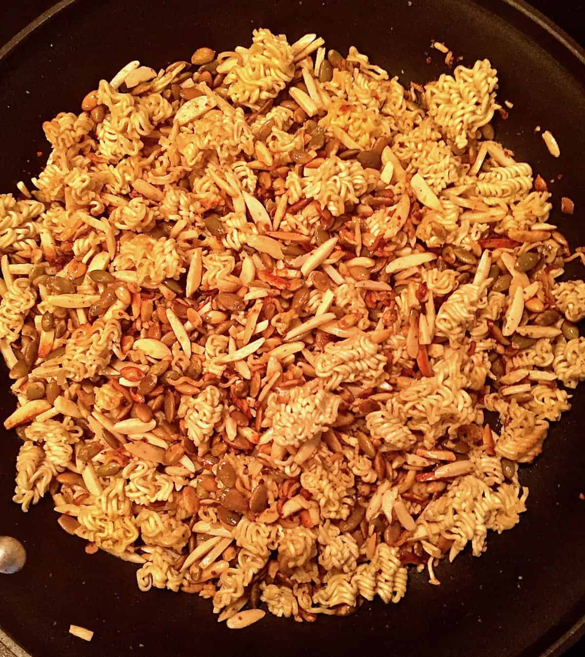 Crushed ramen noodles, slivered almonds and sunflower seeds in a skillet.