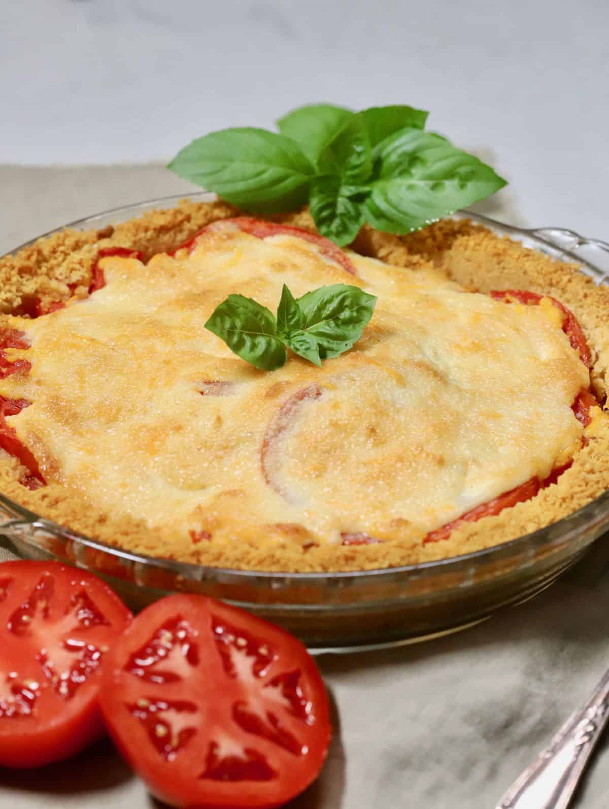 A tomato pie garnished with a sprig of basil.