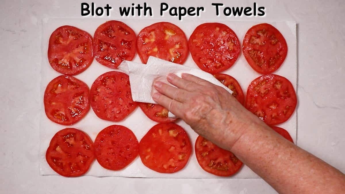 Sliced tomatoes on paper towels draining.
