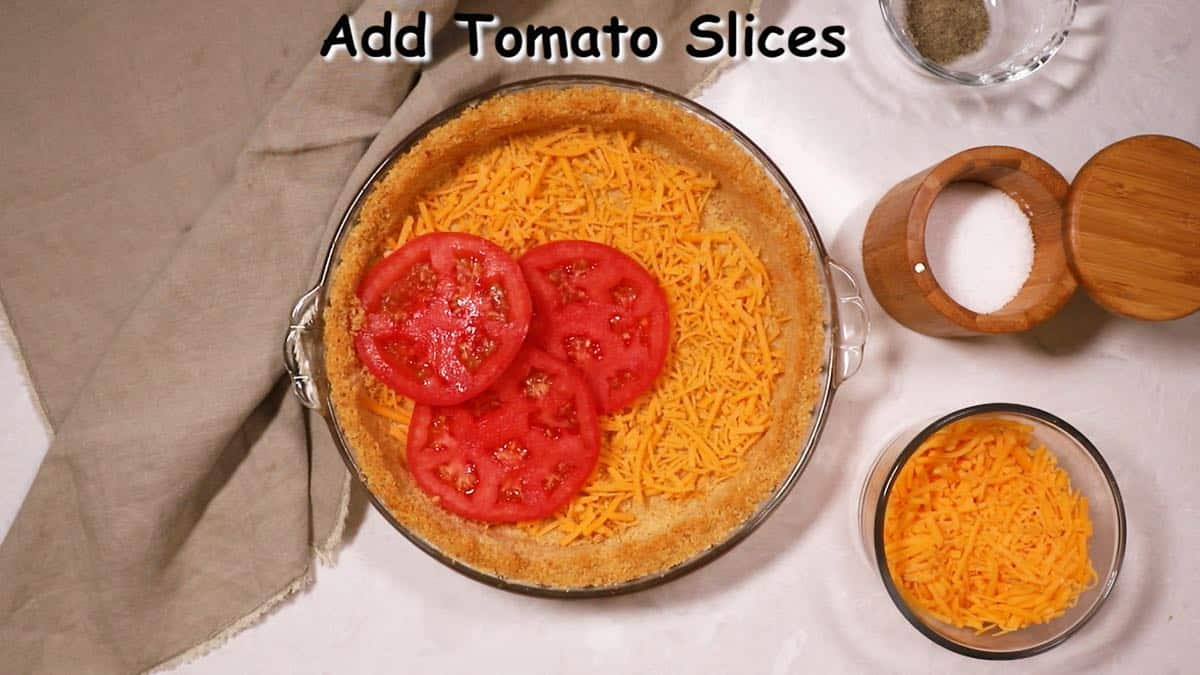 A pie crust topped with a layer of cheese and sliced tomatoes.