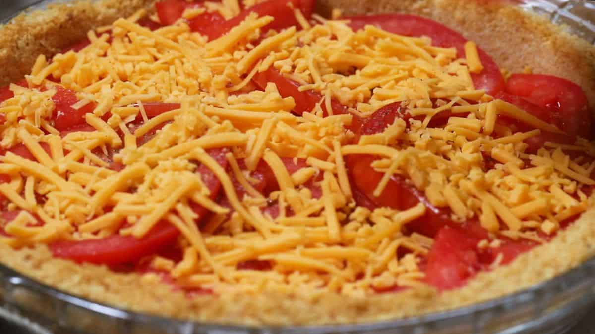 Sliced tomatoes topped with shredded cheese.