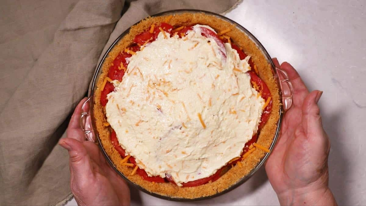 A tomato pie topped with parmesan cheese and mayonnaise mixture.