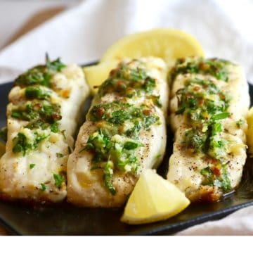Three halibut fillets topped with parsley and lemon zest.