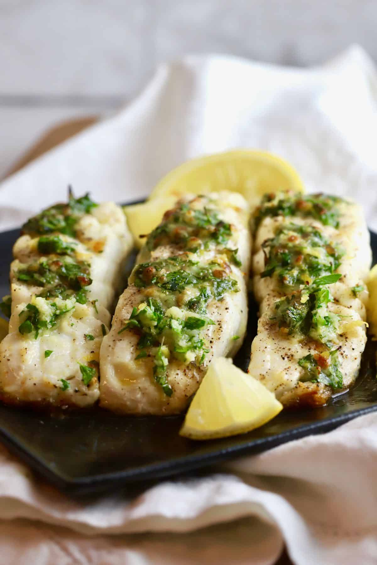 Three broiled halibut fillets on a black plate.