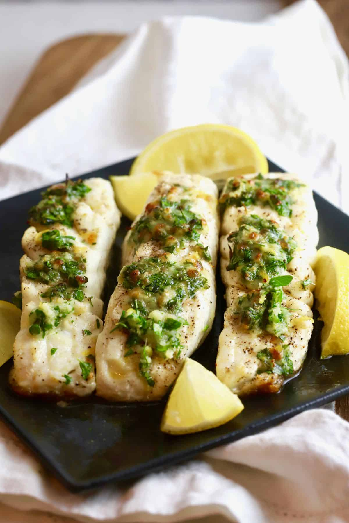 Fish fillets on a black plate garnished with lemon slices.
