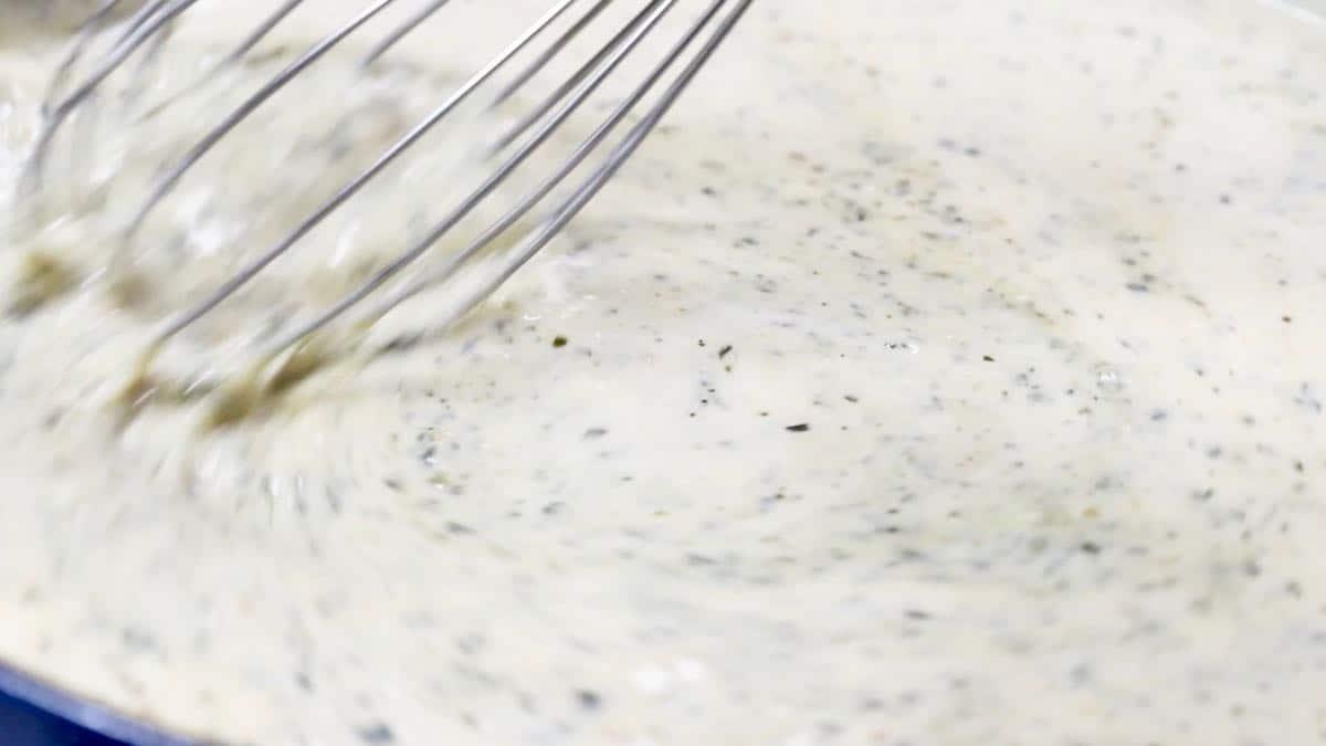 Using a shisk to stir alfredo sauce with pesto.