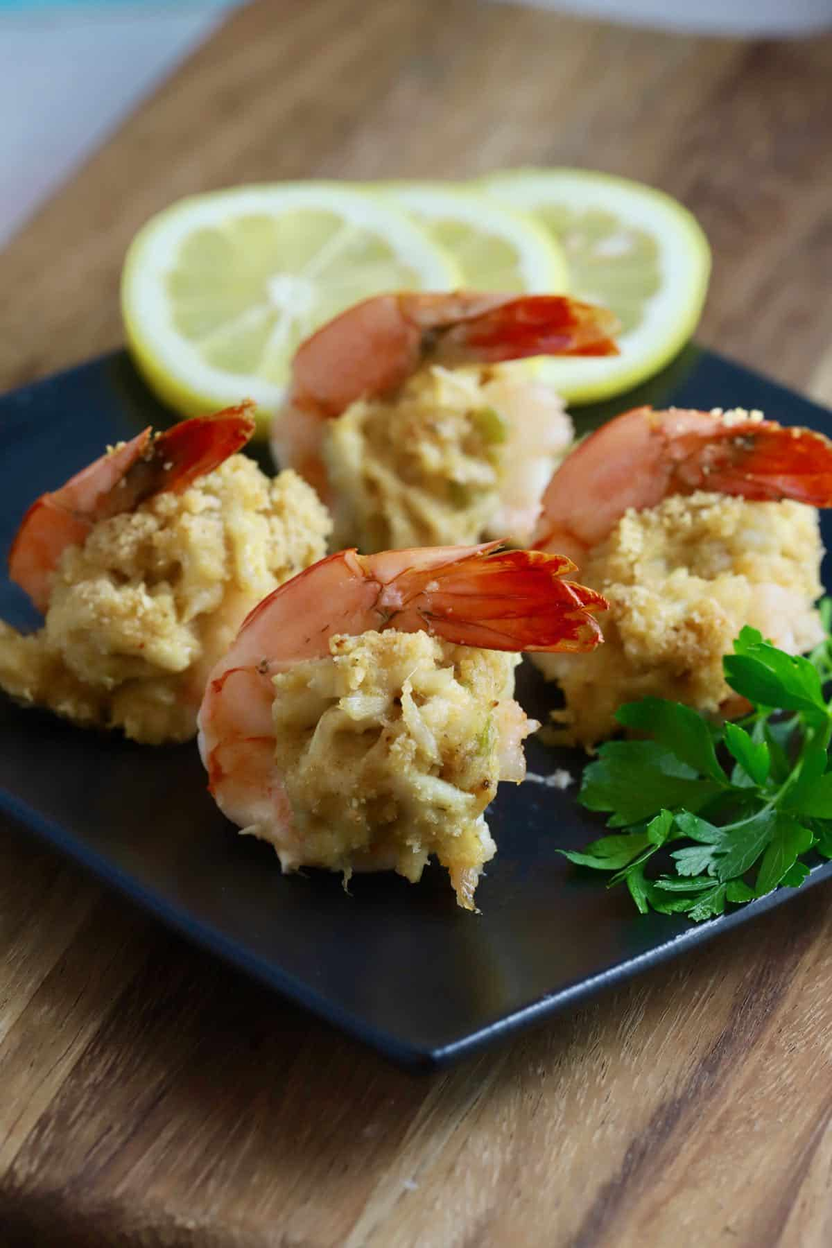 A black plate with four stuffed shrimp.