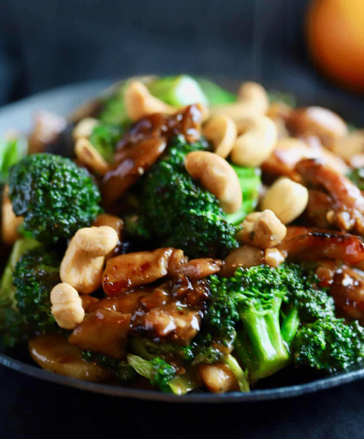 Pieces of chicken and broccoli florets in a black skillet.