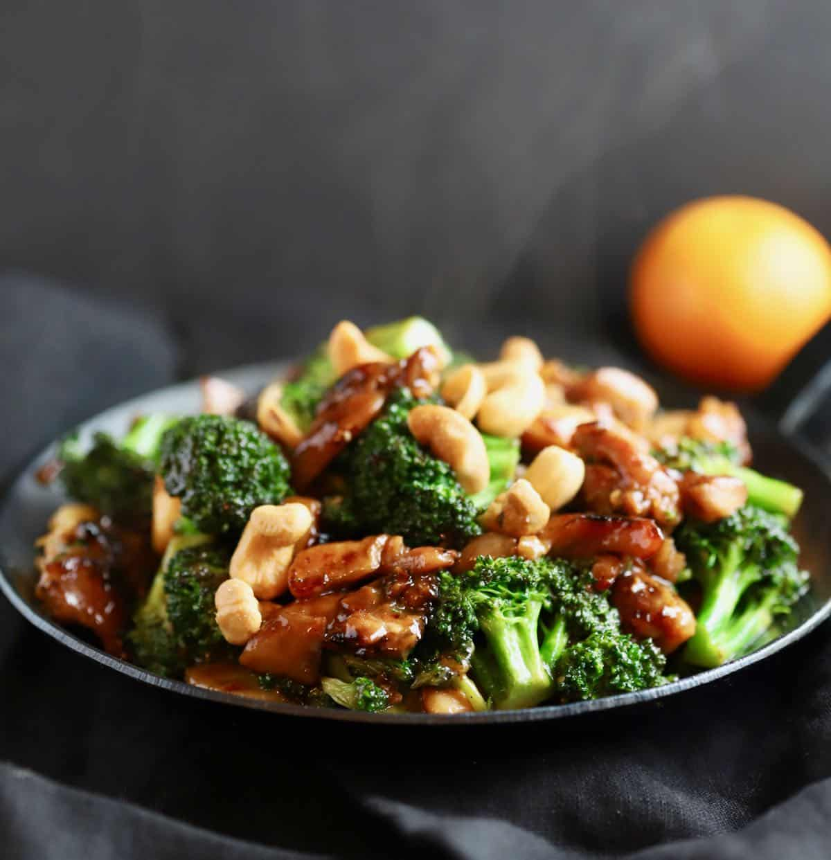 Chicken broccoli stir-fry topped with cashews in a black pan.