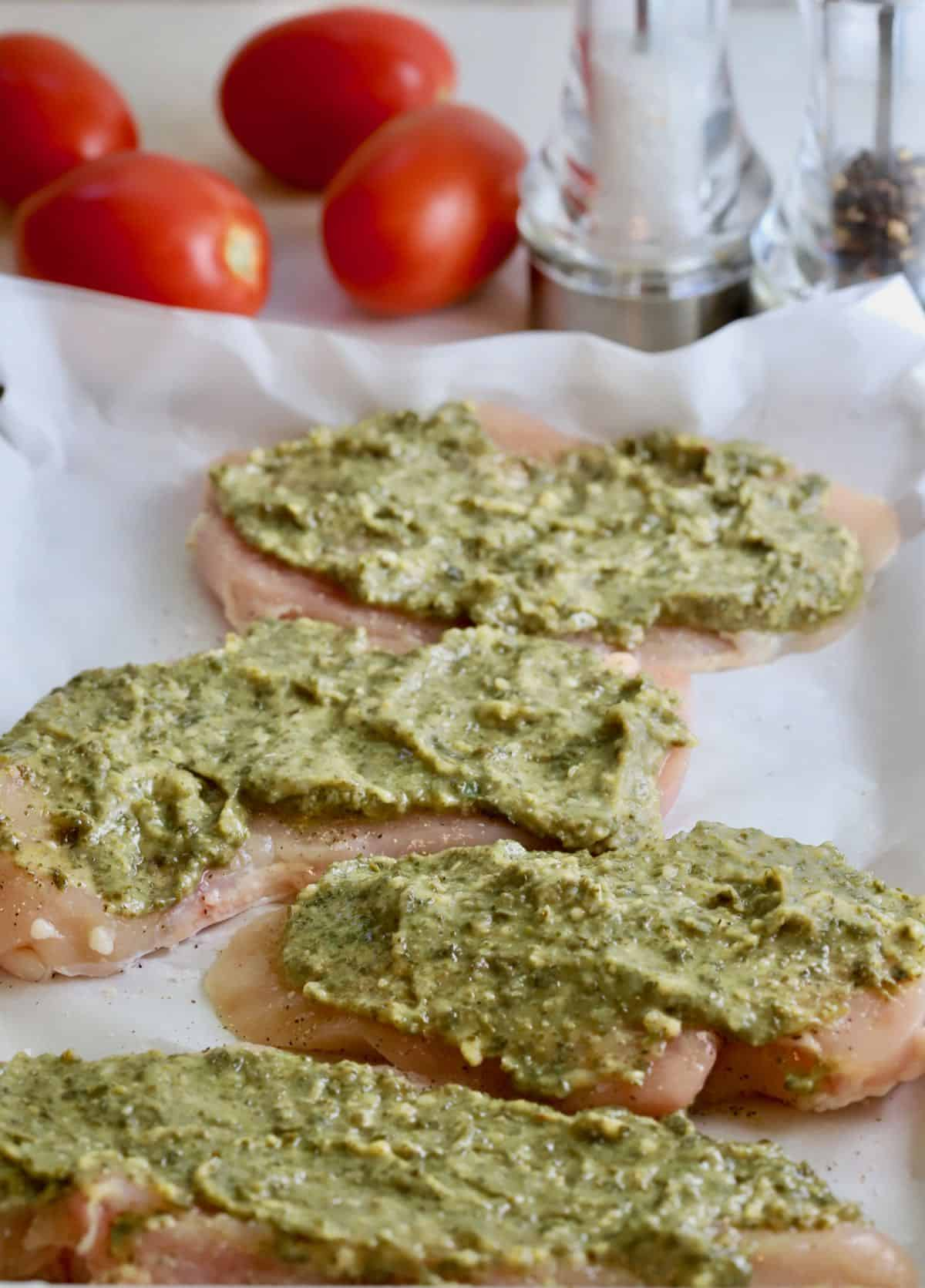 Basil pesto covering chicken breasts.
