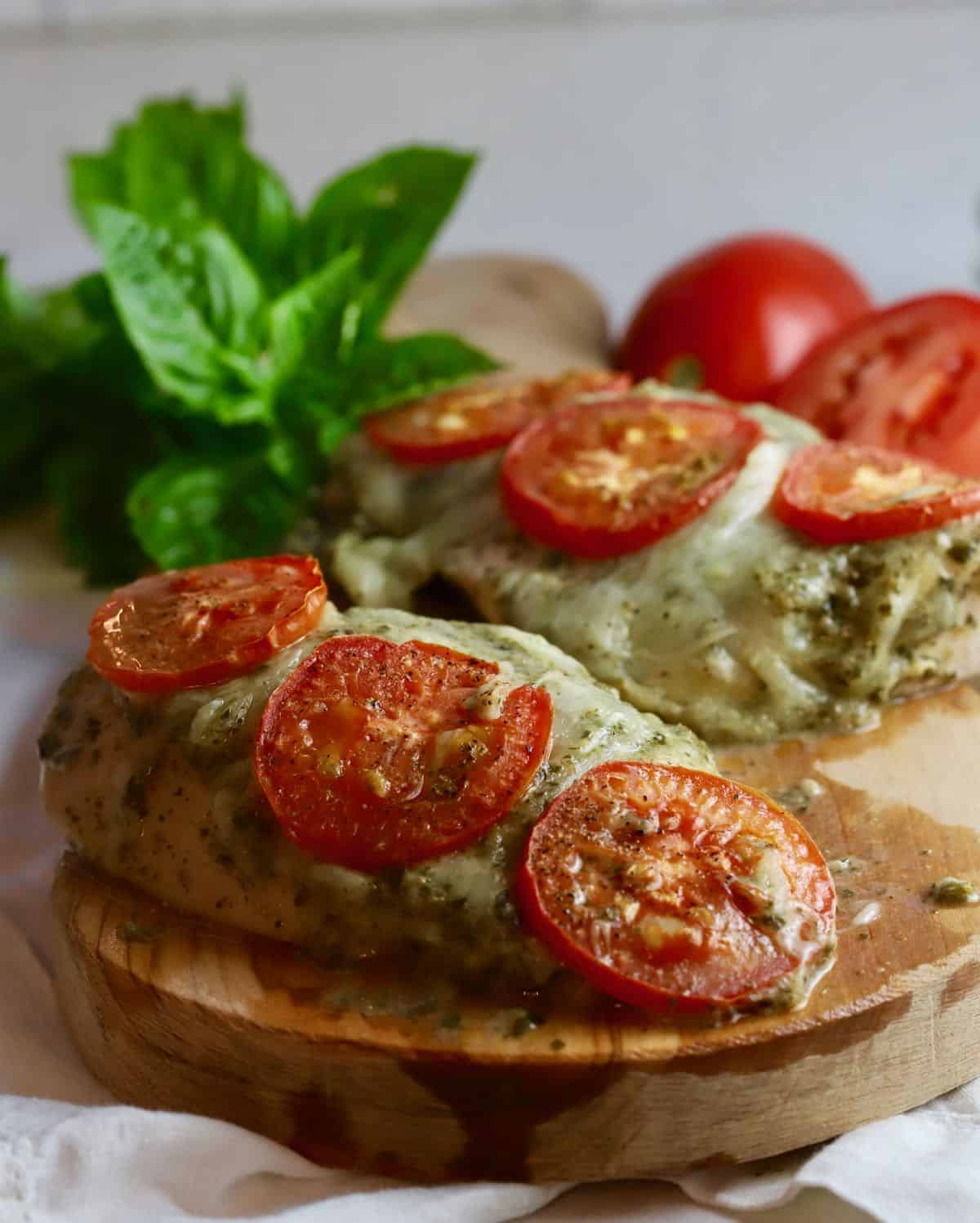 Baked Pesto Chicken on a wooden cutting board.